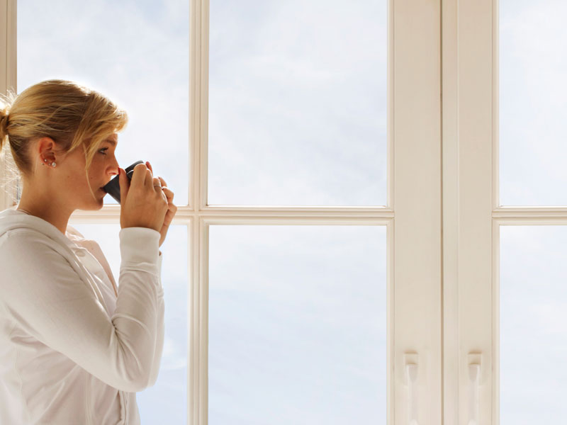 Lady drinking coffee and enjoying her new windows.